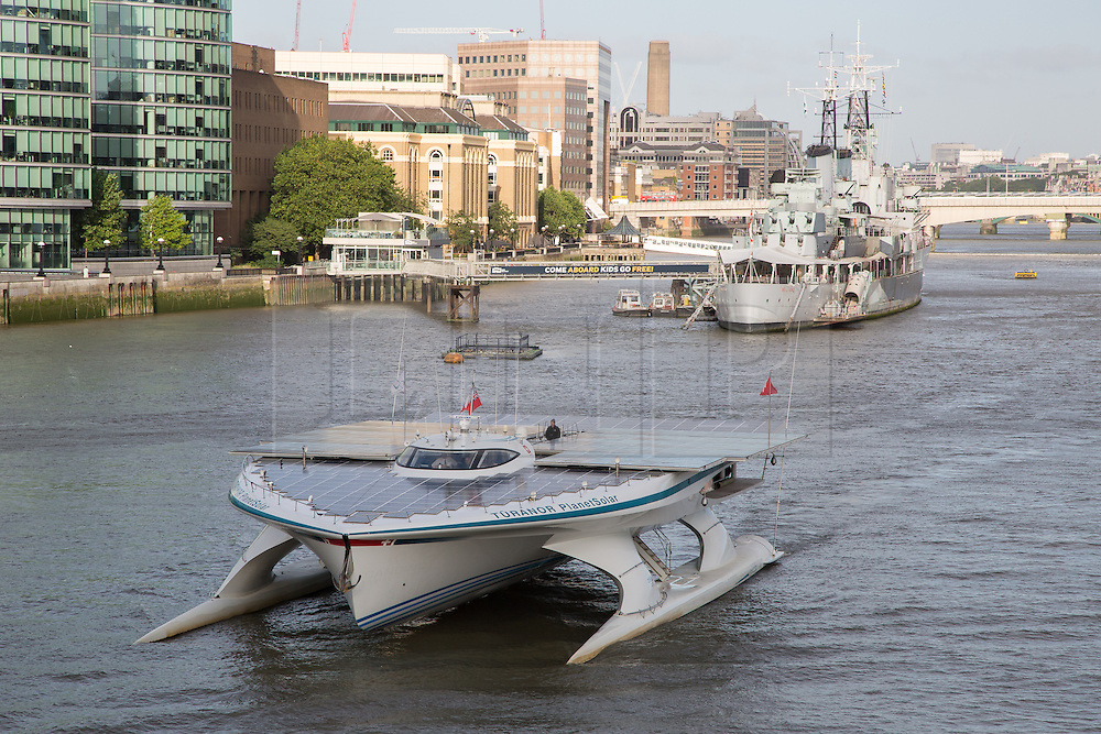 © Licensed to London News Pictures. 31/08/2013. London, UK. MS Tûranor PlanetSolar arrives on the River Thames in London for the first time ever and is seen passing HMS Belfast. MS Tûranor PlanetSolar is the world's largest solar powered vessel and has broken the world record for crossing the Atlantic in 22 days. Its solar panels measure 512 square meters and can generate 480kWh on a sunny day.. Photo credit : Vickie Flores/LNP