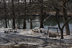 Stock photo of snow covering a picnic area along a river in the Texas Hill Country
