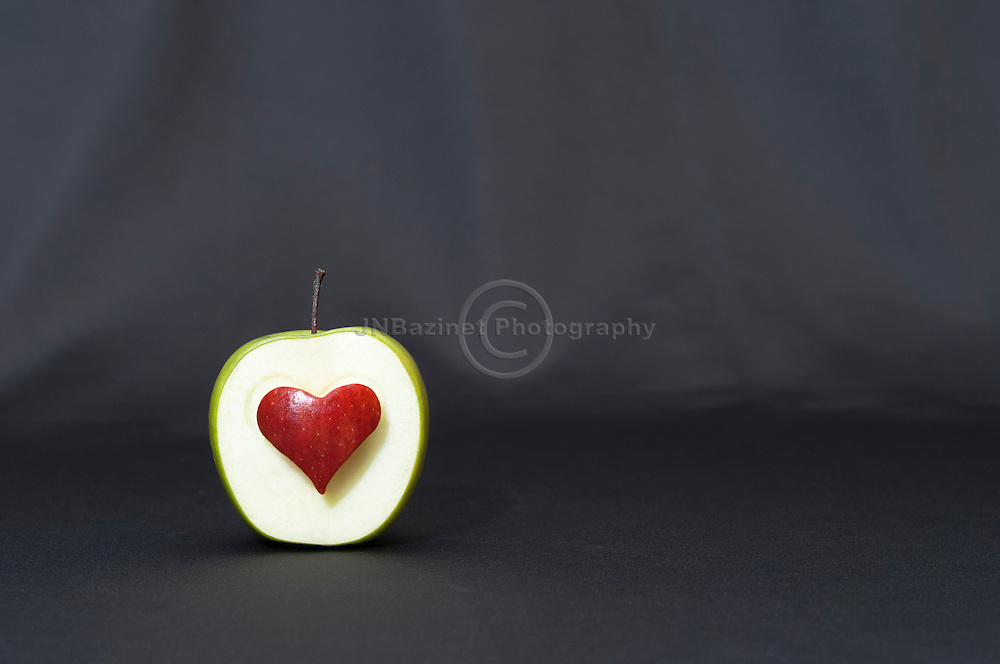 Green apple with cut out of red apple heart