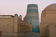 Uzbekistan, Khiva, Ichon-Qala.<br /> Kalta Minor Minaret at dawn with full moon.