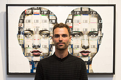 © Licensed to London News Pictures. 13/09/2018. London, UK. Artist NICK GENTRY poses with his work titled Combination 1, 2018 Nick paints portraits on top of obsolete technological materials such as VHS cassettes and floppy disks that contain people's memories. His work is part of a joint exhibiton with South Korea artist SEO YOUNG-DEOK at the Opera Gallery. Photo credit: Ray Tang/LNP