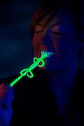 Young girl bites glowing salamander.Black light.Black light