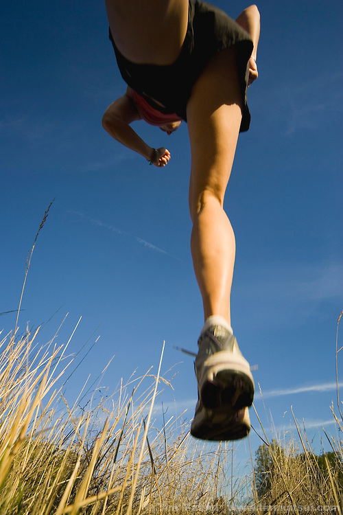 A caucasian woman runs in a field in late afternoon light.