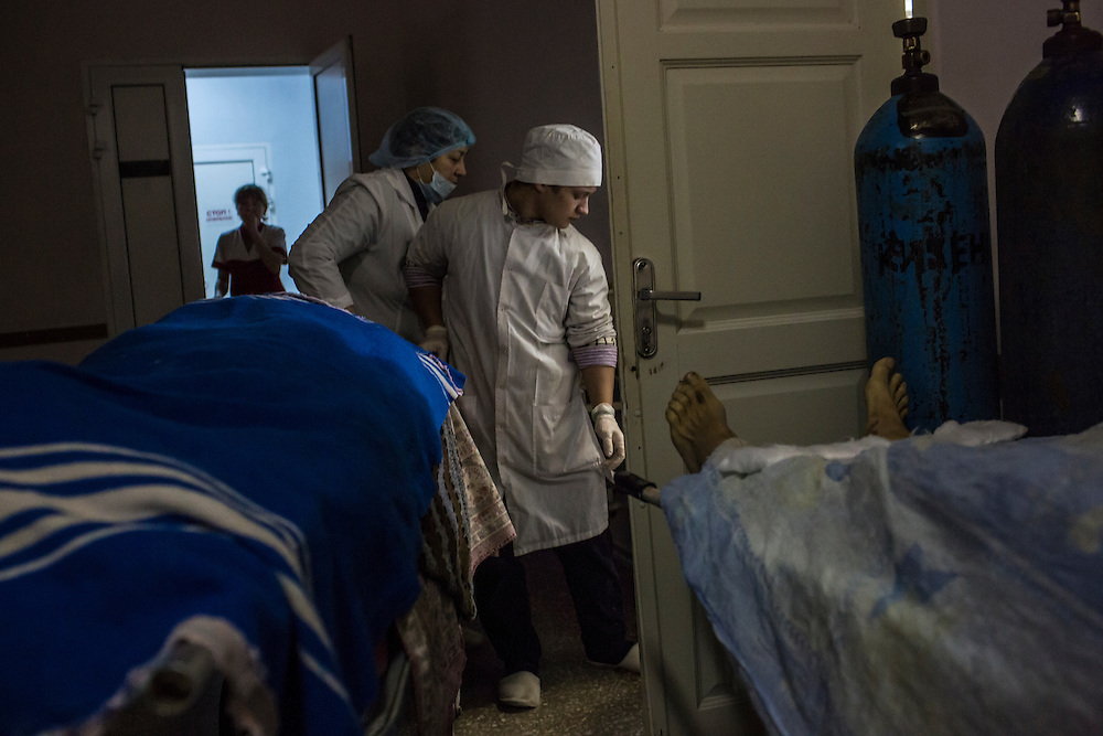 DONETSK, UKRAINE - JANUARY 26, 2015: A woman who was wounded by a rocket attack is wheeled on a gurney into an operating room past the body of her mother, who was killed in the same attack, in Vishnevskogo Hospital in Donetsk, Ukraine. A rocket hit her home, also injuring her nine-month-old daughter. CREDIT: Brendan Hoffman for The New York Times