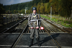 © Licensed to London News Pictures. <br /> 15/10/2016. <br /> Levisham, UK.  <br /> <br /> A re-enactor dressed as a German soldier controls traffic across the railway line at Levisham station during the North Yorkshire Moors Railway Wartime Weekend event. <br /> The annual event brings together re-enactors and enthusiasts along the length of the NYMR heritage steam railway line to recreate the feel of the war years of the 1940's. <br /> <br /> Photo credit: Ian Forsyth/LNP