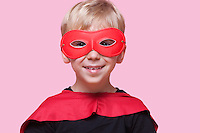 Portrait of a happy boy in superhero costume over pink background
