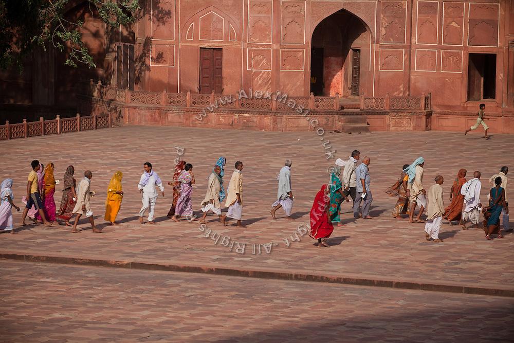 Visitors are walking across the Taj Mahal complex, in Agra.