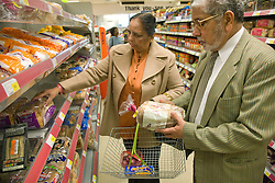 Older couple selecting bread in a supermarket,