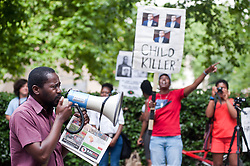 """Zimmerman's trial began on June 10, 2013, in Sanford. On July 13, 2013, he was found not guilty of second-degree murder and of manslaughter charges of Trayvon Martin.<br /> A demonstrator speaks on the megaphone while a woman holds a placard reading """"Child Killer"""" outside the American Embassy to protest the recent Trayvon Martin's Verdict,<br /> London, United Kingdom<br /> Tuesday, 16 July 2013<br /> Picture by Piero Cruciatti / i-Images"""