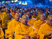 23 NOVEMBER 2014 - BANGKOK, THAILAND: Buddhist monks pray during a mass alms giving ceremony in Bangkok Sunday. 10,000 Buddhist monks participated in the ceremony on Rajadamri Road in front of Central World shopping mall. The alms giving was to assist Buddhist temples in the insurgency wracked southern provinces of Thailand, where Buddhist monks on their alms rounds have been targeted by Muslim extremists. The ceremony was sponsored by Wat Phra Dhammakaya, the center of the Dhammakaya Movement, a Buddhist sect founded in the 1970s. The temple has become active in Thai politics.    PHOTO BY JACK KURTZ