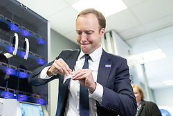 "© Licensed to London News Pictures .FILE PICTURE DATED 06/09/2018. Salford , UK . Secretary of State for Health and Social Care MATT HANCOCK opens a mocked prescription of packaged ""pills"" from an automated medicine dispensing machine during a visit to Salford Royal Hospital (formerly Hope Hospital) at a meeting of software and technology developers working within the NHS . Photo credit : Joel Goodman/LNP"