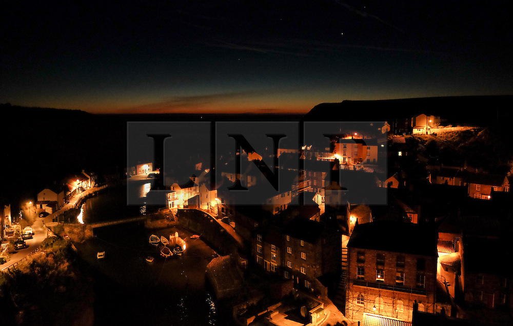 © Licensed to London News Pictures.02/10/15<br /> Staithes, UK. <br /> <br /> Street lights shine on houses as dawn breaks in the North Yorkshire village of Staithes on the east coast as the warm autumn weather continues.<br /> <br /> Photo credit : Ian Forsyth/LNP