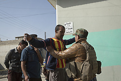November 11, 2016 - Mosul, Nineveh, Iraq - 11/11/2016. Mosul, Iraq. A soldier, of the Iraqi Army's 9th Armoured Division, searches a man in Mosul's Al Intisar district as residents queue to receive food from local volunteers. The Al Intisar district was taken four days ago by Iraqi Security Forces (ISF) and, despite its proximity to ongoing fighting between ISF and ISIS militants, many residents still live in the settlement without regular power and water and with dwindling food supplies...The battle to retake Mosul, which fell June 2014, started on the 16th of October 2016 with Iraqi Security Forces eventually reaching the city on the 1st of November. Since then elements of the Iraq Army and Police have succeeded in pushing into the city and retaking several neighbourhoods allowing civilians living there to be evacuated - though many more remain trapped within Mosul. (Credit Image: © Matt Cetti-Roberts via ZUMA Wire)