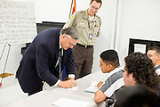 "06 NOVEMBER 2006 - PHOENIX, AZ: Maricopa County Sheriff JOE ARPAIO signs an autograph for a Spanish speaking prisoner in the county jail.  Sheriff Arpaio is offering intensive two week English classes for Spanish speaking prisoners in the Maricopa County Jails so county prisoners can communicate with Detention Officers. The classes teach ""jail English"" so inmates can report medical problems, request their lawyers, request bedding etc. There are more than 1,000 illegal immigrants in the county jail system. In 2011, the US Department of Justice issued a report highly critical of the Maricopa County Sheriff's Department and the jails. The DOJ said the Sheriff's Dept. engages in widespread discrimination against Latinos during traffic stops and immigration enforcement, violates the rights of Spanish speaking prisoners in the jails and retaliates against the Sheriff's political opponents.      PHOTO BY JACK KURTZ"