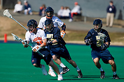 Virginia midfielder Brian Mcdermott (26) is pursued by Navy attackman Kyle Kapron (33).  The Virginia Cavaliers scrimmaged the Navy Midshipmen in lacrosse at the University Hall Turf Field  in Charlottesville, VA on February 2, 2008.