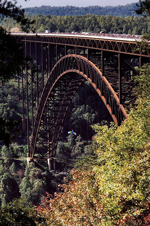 """New River Gorge Bridge, West Virginia, USA. BASE jumper in mid-parachute seen below the 900-foot bridge. BASE jumping is the sport of using a parachute to jump from fixed objects. """"BASE"""" is an acronym that stands for the four categories of objects from which one can jump; (B)uilding, (A)ntenna (an uninhabited tower such as an aerial mast), (S)pan (a bridge, arch or dome), and (E)arth (a cliff or other natural formation). BASE jumping is much more dangerous than skydiving from aircraft and is currently regarded as a fringe extreme sport. -from Wikipedia."""