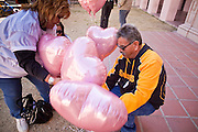 tucsonshooting - 09 JANUARY 2011 - TUCSON, AZ: Alicia Tapia-Cramer (CQ) and her husband, Orlando Cramer, place balloons and candle in downtown Tucson Sunday after a prayer service for Congresswoman Gabrielle Giffords and other victims of the mass shooting that took place Saturday.   ARIZONA REPUBLIC PHOTO BY JACK KURTZ