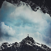 Dreamy mountain scene with a person standing on a peak - photomanipulation