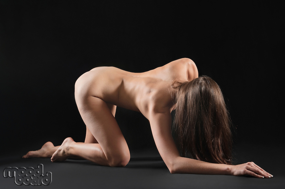 Naked young woman crawling on hands and knees over black background