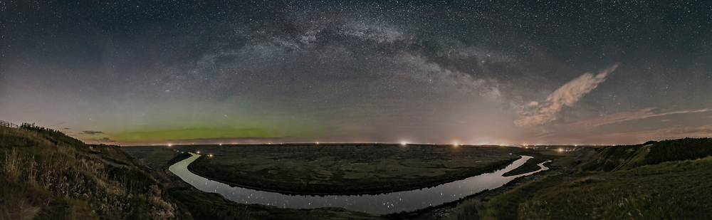 The &ldquo;river of stars&rdquo; &ndash; the Milky Way &ndash;&nbsp;arching over the scenic bend of the Red Deer River, Alberta, from the Orkney Viewpoint overlooking the Badlands and river valley, in a 270&deg; panorama. To the north at left, a weak aurora shines along the horizon. Bands of airglow also colour the sky to the east at centre, and perpetual twilight lights the sky at far left. <br /> <br /> To the south at right, the Milky Way becomes lost amid the light pollution from Drumheller, Alberta, made more obvious by some clouds drifting through. <br /> <br /> So this is a study in skyglows: aurora, twilight, airglow, Milky Way and urban skyglow, and of the contrast between the natural sky and light polluted sky. <br /> <br /> And of course, I like the way the curve of the Milky Way is mirrored in the curve of the river, which is why I picked this spot and this night in spring, when the Milky Way is still arching across the east and not overhead as it is later in summer. <br /> <br /> The most prominent stars reflected in the still waters of the rive are the stars of Delphinus the Dolphin, but there are no dolphins in this river! Only ones made of stars. <br /> <br /> This is a stitch of 8 segments with the Sigma 20mm Art lens, in portrait mode, and Nikon D750. Each 30 seconds at f/2 and ISO 3200. Stitched with Adobe Camera Raw. Taken on a mild and moonless night, May 20, 2017. This version of the image has been processed to make the view better resemble what you see with the unaided eye, in a largely monochrome and softer view than the colourful and high-contrast views commonly presented in astrophotos. Even at that there is more fine structure present in the Milky Way than the unaided eye usually sees, though binoculars beging to reveal that smaller detail. I have left some colours in some stars and in the foreground of landscape scenes.