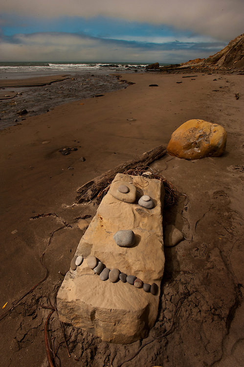 Artwork is displayed on a beach, near Highway 1, at Mendocino California.
