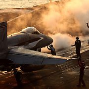"Flight deck Sailors perform final checks on an F/A-18C Hornet from the ""Gunslingers"" of Strike Fighter Squadron  (VFA) 105 while the aircraft, piloted by Commander Carrier Air Wing Three (CVW) 3 Capt. Pat Rainey, is guided to one of the bow catapults on the flight deck of the Nimitz-class aircraft carrier USS Harry S. Truman (CVN 75)."