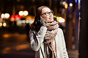Portrait of young attractive woman talking on smartphone at night shopping
