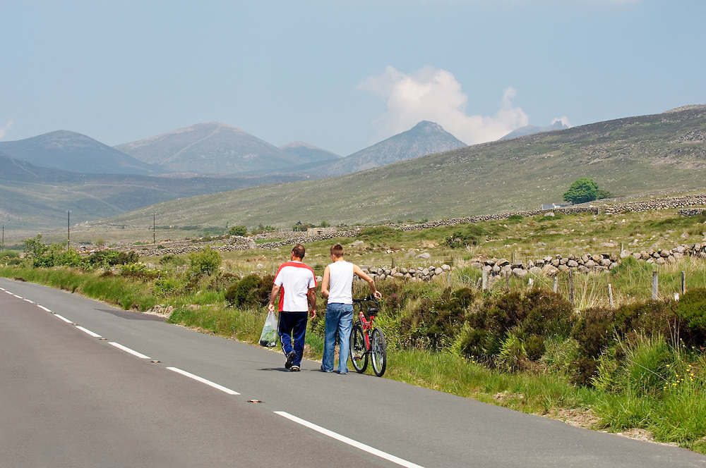 Two men walk the country road north from Attical in the southern Mourne Mountains, County Down, Ireland.