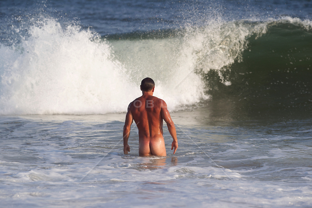 naked man in the ocean