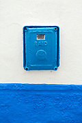 Vintage electrical and water meter boxes, Northern Morocco, 2015-08-11.<br /><br />Asilah is a sleepy fishing town in the North of Morocco, just one hour south of Tangier. While not completely off Morocco's well-beaten path, it's often missed by travellers bound inland for Fez or Chefchaouen, yet has a uniquely alluring charm. With an immaculately restored medina that's re-painted vivid shades of blue & white each summer, Asilah has the feel of being Morocco's own Santorini - a great spot to see the more chilled out, seaside town life in Morocco.  <br /><br />Asilah is synonymous with art and the peaceful seaside town is home to over 50 resident artists. It is packed full of art galleries, studios and exhibition spaces with artists from around the country selling their work. Each summer, the town invites artists from across the globe to visit and take part in an annual arts festival. The festival begins in July and commences by the artists and locals re-painting the medina. They purposefully leave large spaces of the medina walls white-washed blank, ready for artists to create and design new murals and street art during the festival. Artwork can be found everywhere, including sketches and engravings etched onto doorways and walls by children. Large sections are even allocated for children to paint their own ideas and fun workshops are held encouraging children to work together and help paint new murals onto the walls. This is actually how Asilah began its synonymous relationship with art. In 1978 seven Moroccan artists were invited to the town to hold art classes for children, inviting them to draw on the walls of the medina. The festival goes on for a number of weeks showcasing a range of artistic disciplines, from music and poetry to performance and painting, and everything inbetween. Its mark is left on the town for the remainder of the year, as the murals and artwork are left spread throughout the medina, hiding down different alley ways and backstreets for you 