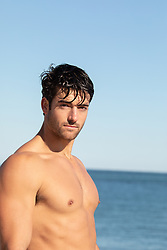 shirtless man by the ocean