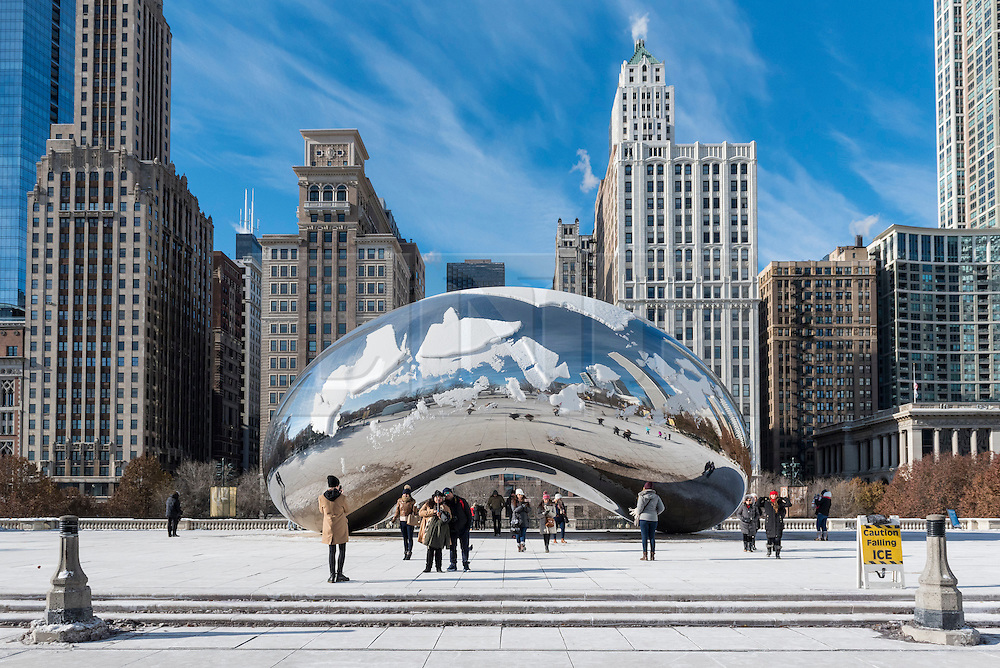 """© Licensed to London News Pictures. 15/12/2016. Chicago, USA. The city of Chicago suffers the first severe cold of the year with daytime temperatures of -5F or -15C recorded.  Tourists continue to brave the low temperatures to visit some of the city's iconic landmarks, such as Cloud Gate (""""The Bean"""").   Photo credit : Stephen Chung/LNP"""