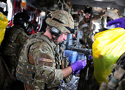 © London News Pictures. 11/06/11. AFGHANISTAN. Cpl Matt Purssey is one of the paramedics on board the MERT.  During one of the call outs he begins to prepare bags of fluid containing blood and plasma, as early reports suggest that the casualty will be a possible amputation. The RAF Regiment's Medical Emergency Response Team (MERT) is made up of two teams based in 'Main Operating Base Bastion', they are responsible for extracting casualties from anywhere within Helmand Province.  The MERT consists of a doctor, an emergency department nurse and two paramedics.  In addition four Royal Air Force Regiment gunners provide armed protection when they land and leave the helicopter to collect the casualty.   Caption must read Alison Baskerville/LNP...