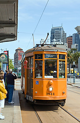 San Francisco, CA:  A Peter Witt vintage trolley from Milan rolls down the F-Line that loops and links Market Street, the Ferry Building, and Fishermen's Wharf.  <br /> <br /> From the Market Street Railway website: &quot;In addition to its world-famous cable car fleet, the San Francisco Municipal Railway (Muni) owns some ninety historic streetcars, trolleys, and trams (names used in different parts of the world to describe electric rail vehicles capable of running on city streets). About half of these streetcars are in active service, or being prepared for it; the remainder are currently non-operational, unrestored cars that could be used for future service expansion.<br /> <br /> Three general types of vintage streetcars are used in San Francisco: a collection of unique vintage cars from both San Francisco and around the world; streamlined art deco PCC streetcars from the 1940s and 1950s that provide the backbone of daily service; and 1920s Peter Witt trams from Milan, Italy, which also operate daily. <br /> <br /> This older type of streetcar was designed by Cleveland transit leader Peter Witt and ran in many US cities, though never in San Francisco. Milan, Italy built hundreds of Peter Witts in 1928 and are still running some today. Muni got one car, No. 1834, as a Trolley Festival gift in 1984 and liked it so much they obtained ten more in 1998 to meet the huge F-line rider demand.<br /> <br /> The Peter Witts entered Muni service still wearing the solid orange livery used in Milan for the past quarter-century. In 2004, however, car No. 1811 was repainted into the original 1928 Milan livery of yellow and white with black trim. In 2007, No. 1818 received the two-tone green livery that the Milan trams wore from the 1930s to the 1970s. Market Street Railway has suggested to Muni that as these cars are repainted, the fleet is balanced between the three historic Milan liveries (yellow, green, and orange). <br /> <br /> Some of the Milan trams retain their original Milan fleet numbers; others have had the second digit changed to 8