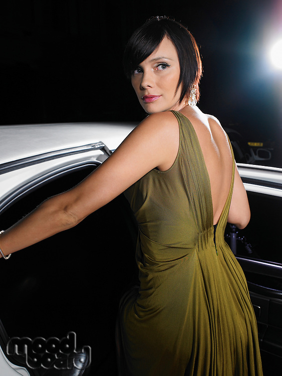 Woman in evening wear getting into limousine