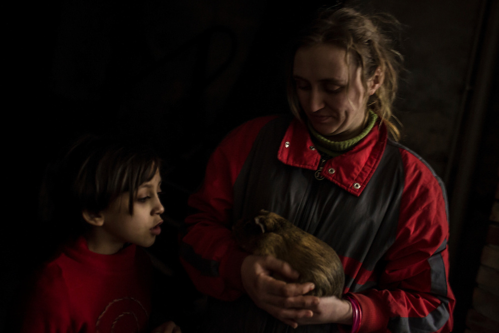 DONETSK, UKRAINE - JANUARY 29, 2015: A woman shows her pet guinea pig to a young girl in the underground bomb shelter where they both currently live in the Petrovskyi district of Donetsk, Ukraine. The neighborhood has been shelled heavily in the past few days, forcing many people back to the shelters they first fled to in the summer. CREDIT: Brendan Hoffman for The New York Times