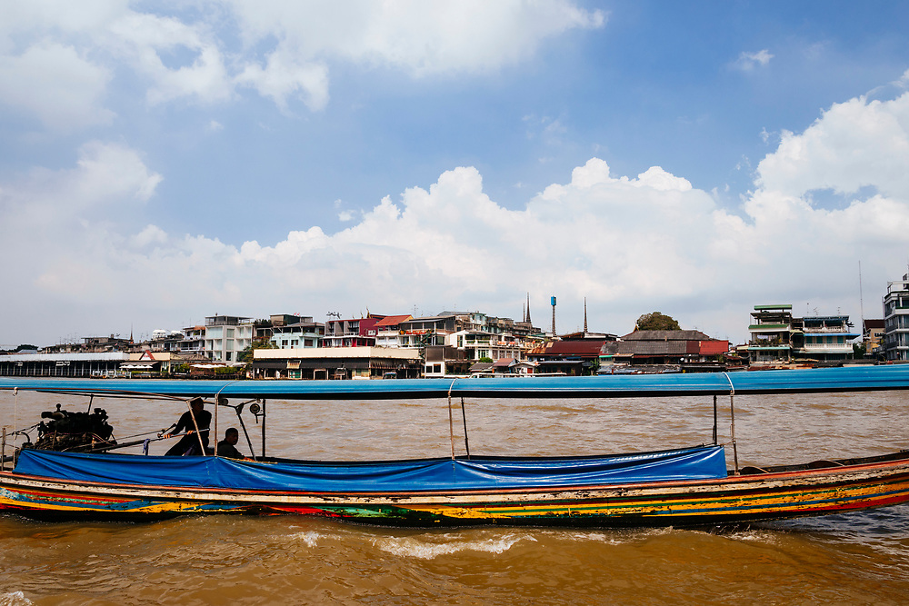 A small boat makes its way down the Chao Phraya river in Bangkok, Thailand.