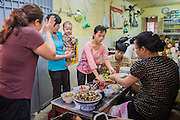 05 APRIL 2012 - HANOI, VIETNAM:   A woman in a noodle shop entertains a baby in Hanoi, the capital of Vietnam.   PHOTO BY JACK KURTZ