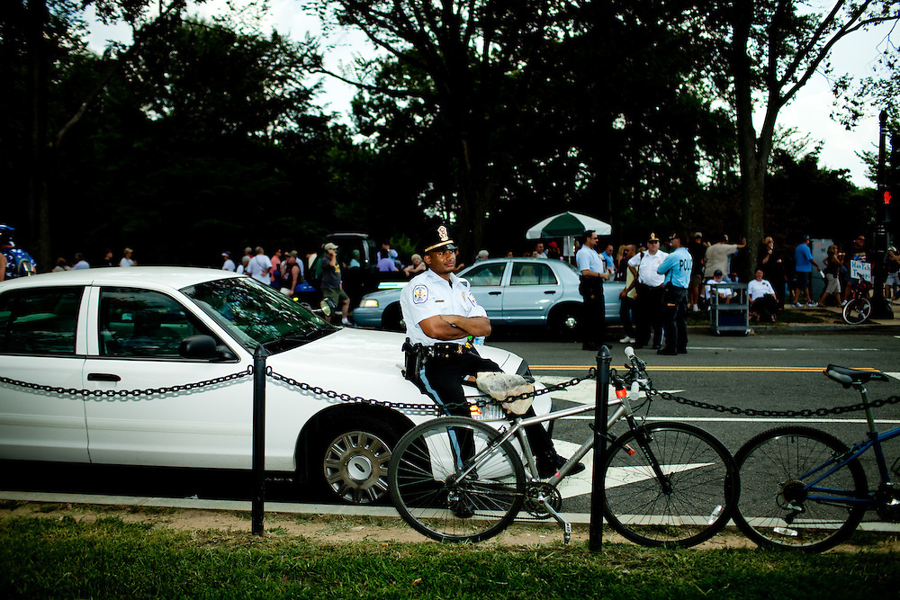 A police officer sits on his car during the 'Restoring Honor' event at the Lincoln Memorial on August 28, 2010 in Washington, DC.