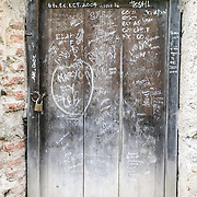 Graffiti on a door at Iglesia y Convento de La Recolección in Antigua, Guatemala.