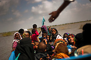 Women and children wait for a boat to ferry them to their village where road access has been cut off by the monsoon floods, on October 4, 2011, in Jhuddho, Pakistan. According to UN reports, hundreds of thousands of children in Pakistan suffer from severe-acute-malnutrition, with 15.1% of children experiencing acute malnutrition. Child malnutrition has breached emergency levels in Pakistan's Sindh province, after monsoon floods devastated the country's poorest region for a second year. Extreme poverty, poor diet and health, exposure to disease, and inadequate sanitation and hygiene annually produce alarming levels of malnutrition amongst children, but the floods have increasingly endangered an already vulnerable population. (Photo by Warrick Page)
