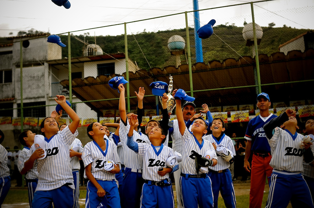 The little league team, Zea, celebrates their second place finish in the championship after being awarded a trophy by the Mets' Johan Santana on the same field where he grew up playing baseball. Santana went back to Tovar, Venezuela last weekend for an annual charity event thrown by the Johan Santana Foundation and passed out 10,000 toys to local children. Before throwing the opening pitch of the little league championship, Santana also surprised every team in the league with new equipment.