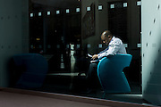 A businessman sits reading documents in sunlight by the wondow of a company foyer in the City of London, the capital's financial district.