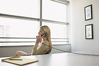Business woman using phone sitting at office desk side view