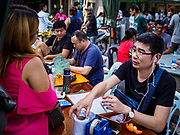 21 DECEMBER 2018 - CHANTABURI, THAILAND: A Chinese gem merchant talks to a customer in the Chantaburi gem market. The gem market in Chantaburi, a provincial town in eastern Thailand, is open on weekends. Chantaburi used to be an active gem mining area in Thailand, but the mines are played out now. Now buyers and sellers come from around the world to Chantaburi for the weekend market. Many of the stones come from Myanmar, others come from mines in Afghanistan and Africa.       PHOTO BY JACK KURTZ