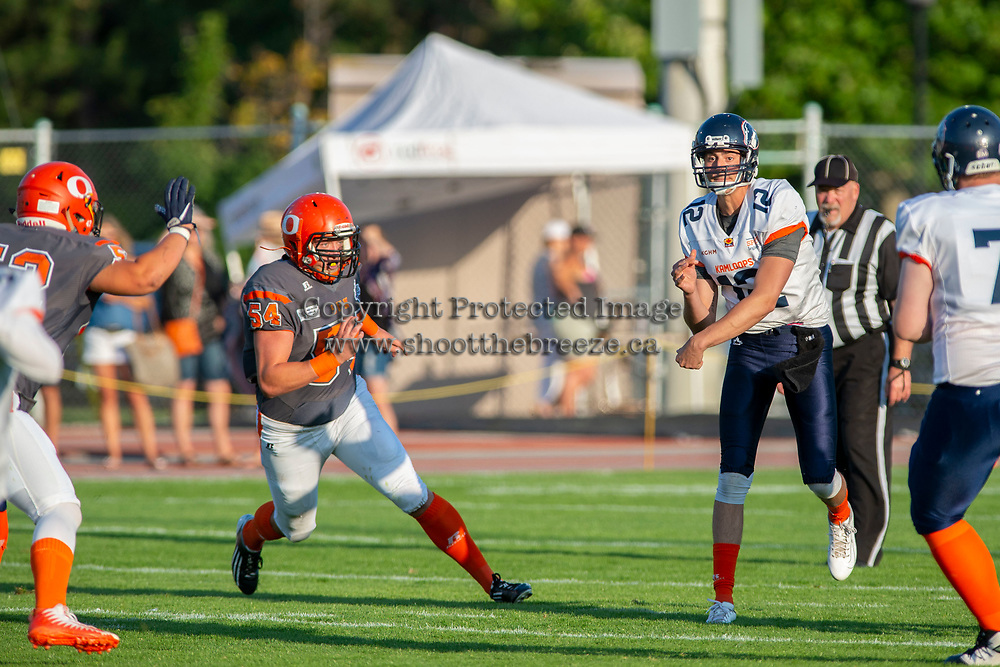 KELOWNA, BC - AUGUST 3:  Cory McCoy #54 of Okanagan Sun runs in to tackle quarterback Nicolas Nica  #12 of Kamloops Broncos at the Apple Bowl on August 3, 2019 in Kelowna, Canada. (Photo by Marissa Baecker/Shoot the Breeze)