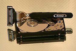 Mirrored image of Gillette Mach 3 razor on opened computer hard drive with gold toned lighting.