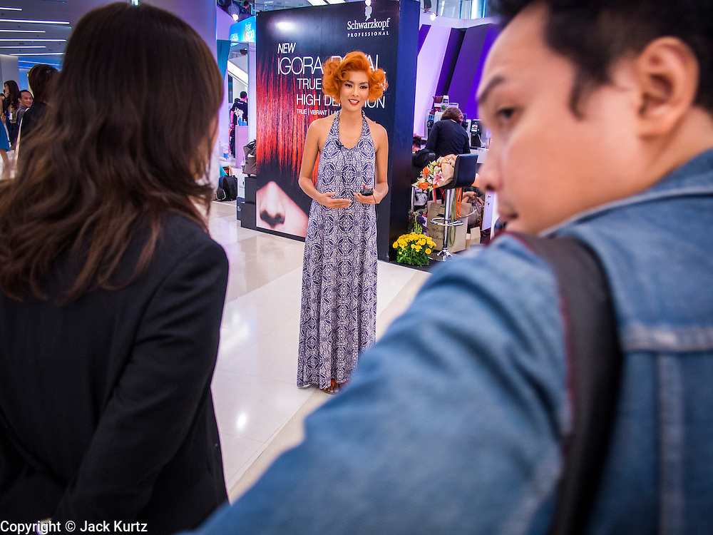 24 JULY 2013 - BANGKOK, THAILAND:  A hair model gives a TV interview at the Hairworld Festival in Siam Paragon, an upscale shopping mall in Bangkok, Thailand.        PHOTO BY JACK KURTZ