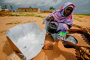 "A woman pours tea in a refugee camp in Touloum in Tchad, close to the sudanese border. The tea is boiled in a solar cooker, manufactured by women in the camp.  More than 23.000 refugees from Darfur, mainly women and children, live in the camp. The benefits of solar cookers are huge: Traditionally women do the hard job of gathering wood for fire. In a barren, conflict ridden area like the Darfur border, the women walk long distances in search of the wood, and are often assaulted and raped. The solar cookers alleviate both the hard work and the dangers facing these women.  <br /> Countries in the SAHEL area are not the big emitters of greenhouse gases. Tchad emitted about 0.5 metric tons in 2013, while the US and China emitted 5233 and 9977 metric tons respectively.<br /> In the draft being presented at the COP21 in Paris, poorer countries demand financial aid to help transition to renewable energy, as well as help to cope with climate change. Countries most at risk also demand a tougher target of 1.5 degrees – a cap supported by climate change scientists. As Penn State climate scientist Petra Tschakert put it, the 2 degree cap is ""utterly inadequate""."