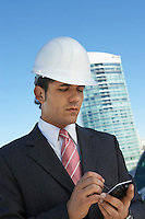 Businessman in hardhat using PDA outdoors